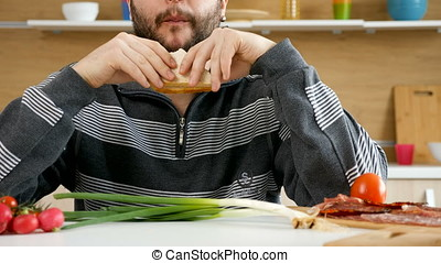 Man eating a club sandwich in the kitchen