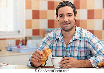 Man eating a continental breakfast