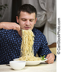 man eating a large portion of pasta
