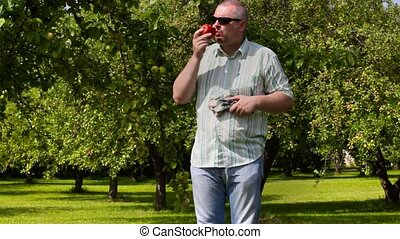 Man eating apple in the garden
