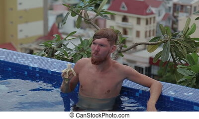 Man eating banana and smiling a roof top luxury swimming pool.