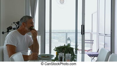 Man eating breakfast on table at home 4k