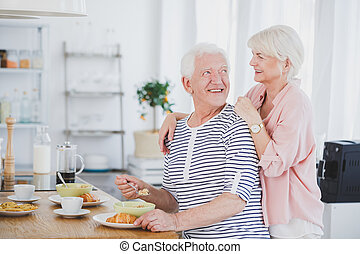 Man eating breakfast with woman behind him