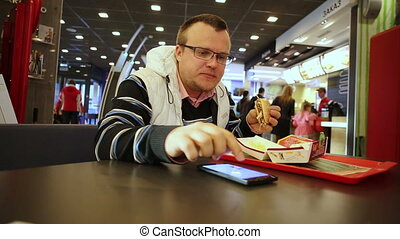 Man eating burger and using smartphone