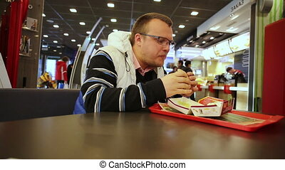 Man eating burger in a fast food restaurant