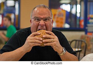 man eating burger in fast food restaurant