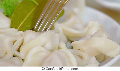 Man eating dumplings with a fork - Meat dumplings served on...