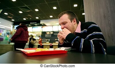 Man Eating Fastfood Burger And French Fries in the cafe