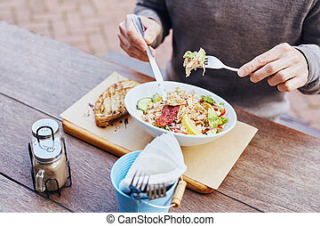 Man eating healthy chicken salad at a cafe