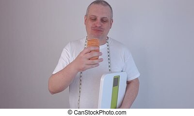 Man eating hot dog and step up on digital scale