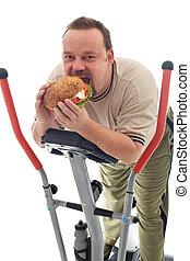 Man eating huge hamburger on a trainer device