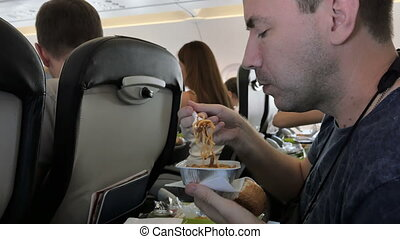 Man eating lunch in airplane. 4k