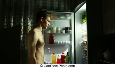 man eating out of the refrigerator at night. eating apple -...