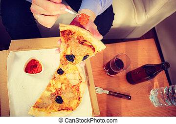Man eating pizza adding tomato sauce