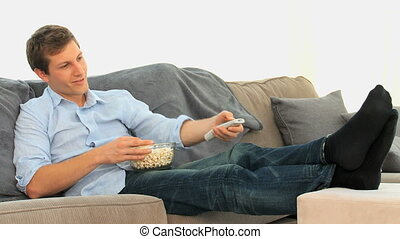 Man eating popcorn in front of tv