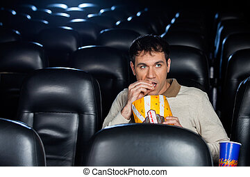 Man Eating Popcorn While Watching Movie In Theater