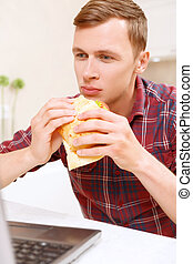 Man eating sandwich in front of computer