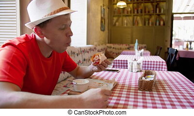 Man eating tacos on a wooden board and sauce, on a table in ...