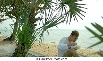 man eating Thai soup Tom Yam sitting on the beach,...
