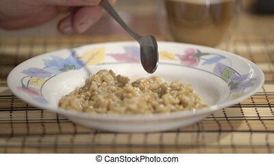 Man eating whole grain oats porridge. Oatmeal healthy...
