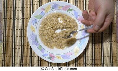 Man eating whole grain oats porridge. Oatmeal healthy breakfast.