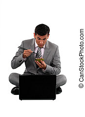 Man eating with chopsticks in front of a computer