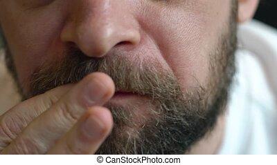 Man eats a hamburger close up - Bearded man eating hamburger...