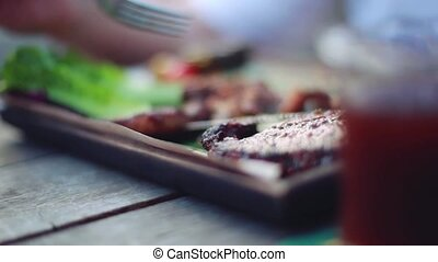Man eats a piece of steak with vegetables close-up on blurred background.