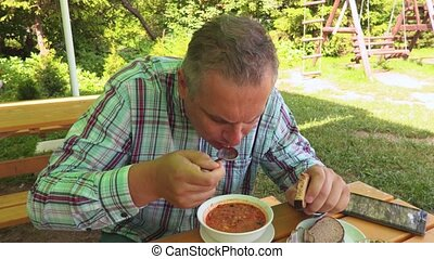 Man eats a soup in outdoor summer cafe