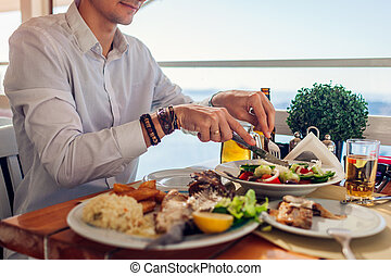 Man eats fish with vegetables in outdoors restaurant. Fresh seafood dinner with sea landscape. Summer vacation