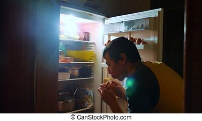 man eats hunger and gluttony from the refrigerator at night. man looks into the fridge at night lifestyle. gluttony overweight overeating concept
