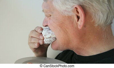man eats jelly doughnut - older man eats a jelly doughnut...