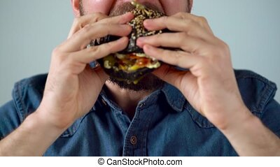 Man eats juicy hamburger - Bearded man eating black juicy...