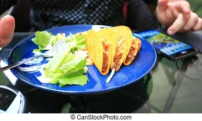 Man eats Mexican tacos in tortilla shells with fresh vegetables and uses phone