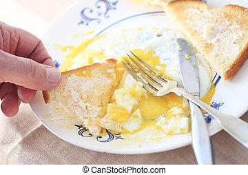 Man eats runny eggs and toast POV