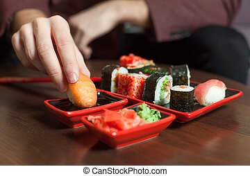 Man eats sushi roll with hands