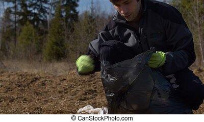Man eco volunteer picking garbage