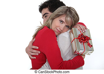 man embracing his girlfriend after giving her a present