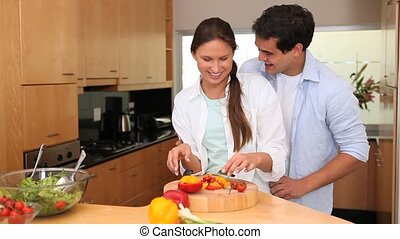 Man embracing his wife who's cutting vegetables