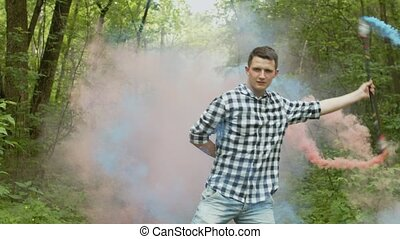 Man emerging from veil of coored smoke among forest -...