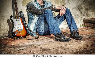 man, en, gitaar, leunende tegen een muur
