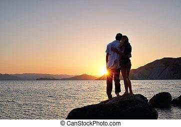 man en vrouw, staand, in, een, omhelzen, en, horloge, de, ondergaande zon