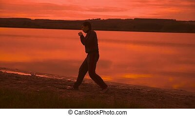 man engaged in melee combat sports boxing at sunset sport...