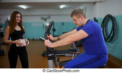 man engaged on a stationary bike, the girl tells him coach on the tablet, fitness healthy lifestyle
