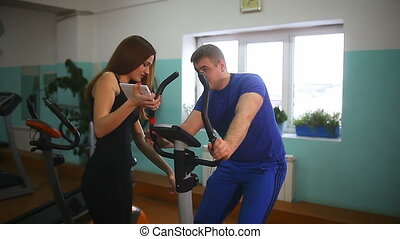 man engaged on stationary bike, the girl tells him coach on...