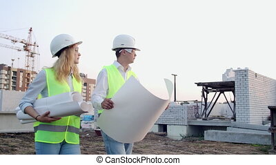 Man engineer and woman architect at a construction site....