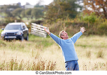 Man Enjoying Freedom Outdoors in Autumn Landscape