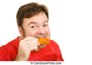 Man Enjoying Hot Wings - Middle aged man in football jersey...
