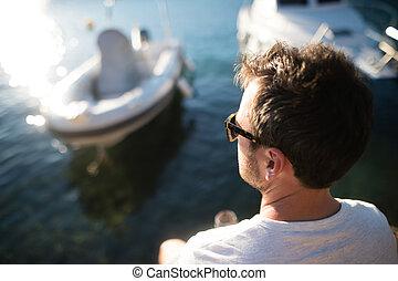 Man enjoying time at seaside, sitting on wooden pier.