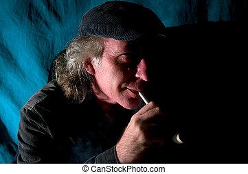 man enjoying tobacco pipe in dark room